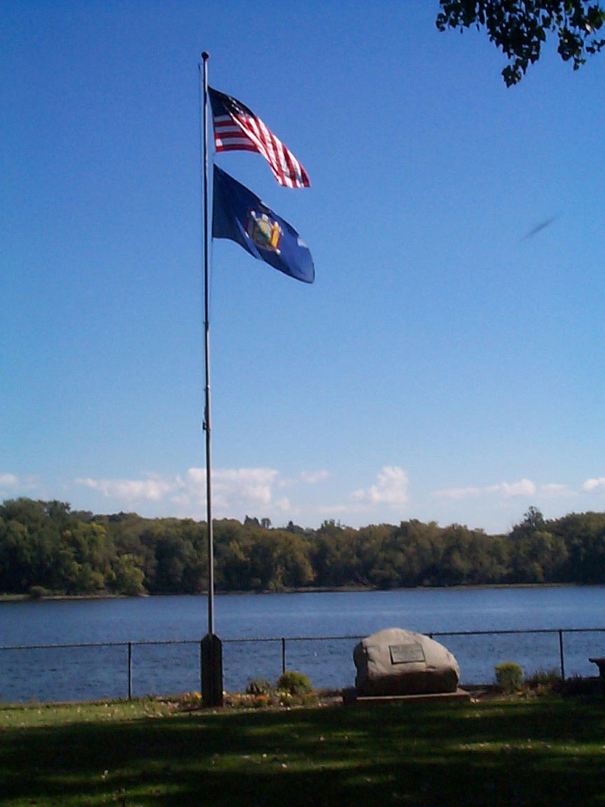 Stone Marker and flags on the shore of the Hudson River at Henry Hudson Park